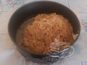 Измельченное песочное печенье с маслом в форме для чизкейка